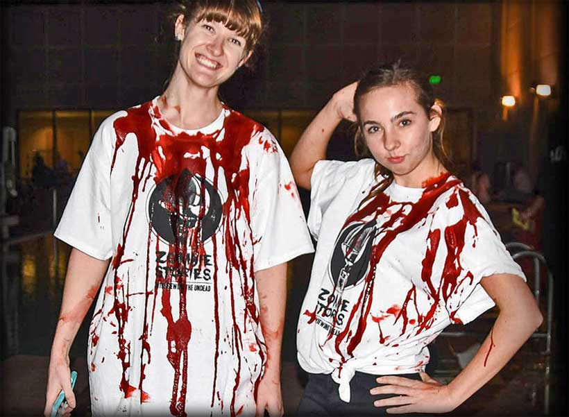 Two college students wearing Zombie Stories shirts, covered in fake blood.