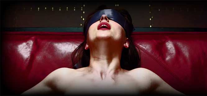 A woman with a blindfold on lies against a red leather couch enjoying her S&M.