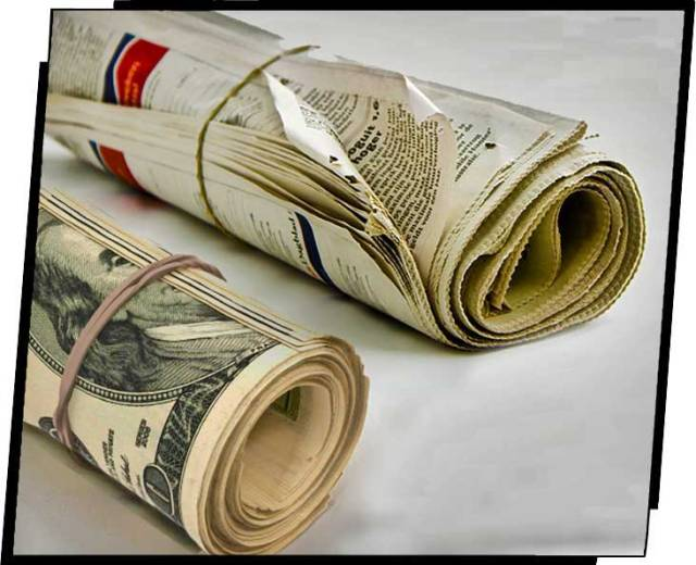 Rolled-up newspaper and rolls of bills